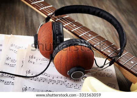 Electric guitar with headphones and musical notes on wooden background - stock photo
