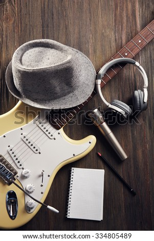 Electric guitar with headphones, hat and microphone on wooden background - stock photo