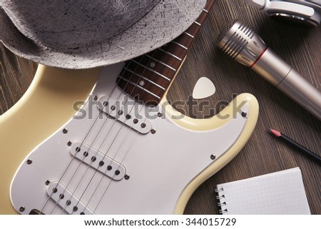 Electric guitar with headphones, hat and microphone on wooden background, close up - stock photo