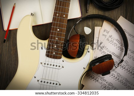 Electric guitar with headphones, musical notes and note book on wooden background - stock photo