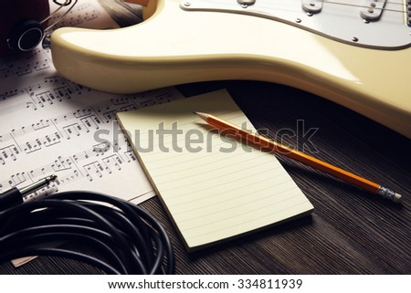 Electric guitar with musical notes, pencil and sheet on wooden background - stock photo