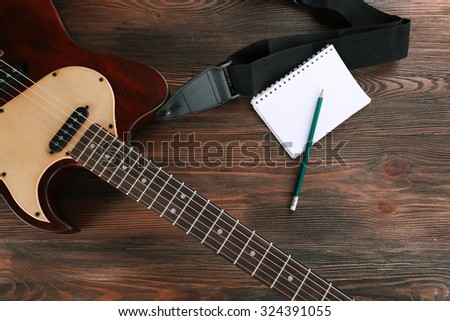 Electric guitar with notebook on wooden table close up - stock photo