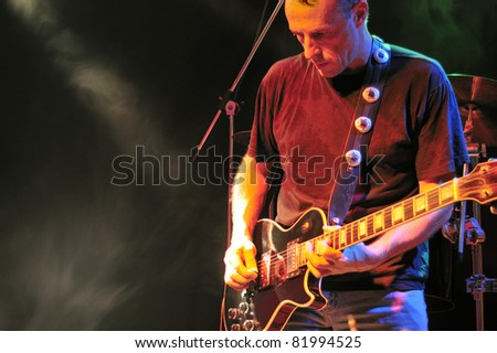 Electric guitarist on stage. Sweating, concentrating. - stock photo