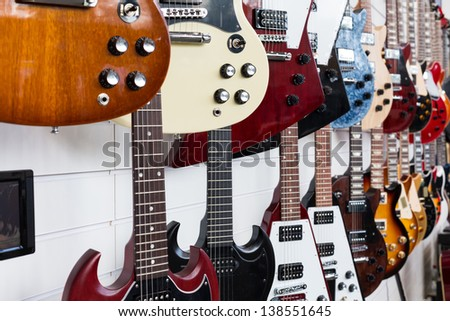 Electric guitars hanging on wall in the shop - stock photo