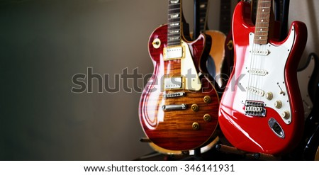 Electric guitars resting on a guitar stand in a darkish room or studio, with plenty of copy space.Shallow depth of field.   - stock photo