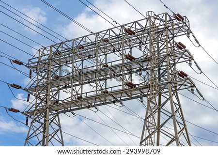 Electric industry power and energy transmission tower or electricity pylon steel lattice grid structure. Array of wires, conductors and insulators. Blue sky and clouds background.  - stock photo