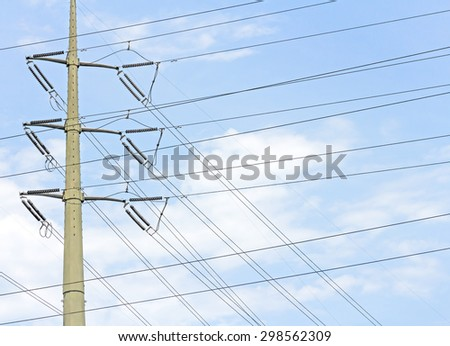 Electric industry power and energy transmission tower or electricity pylon structure. Array of overhead criss crossed wires, conductors and insulators. Blue sky and clouds background.  - stock photo