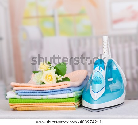 Electric iron and colorful towels on the background of the ironing room. - stock photo