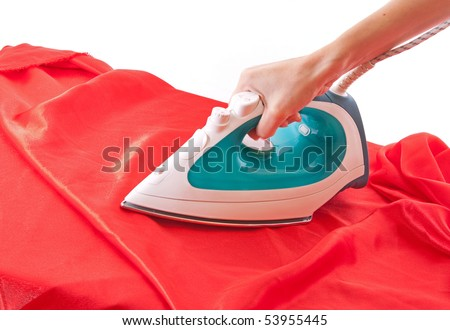 Electric iron on red cloth isolated on white - stock photo