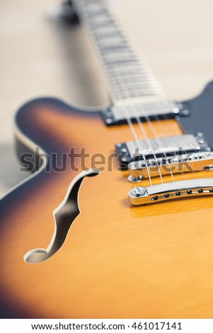 Electric jazz guitar close up on an orange sunburst color and chrome electronics