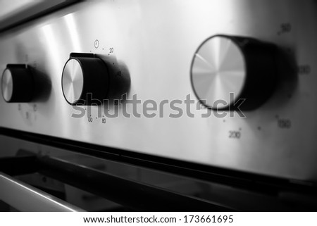 electric kitchen stove control switch, black and white - stock photo