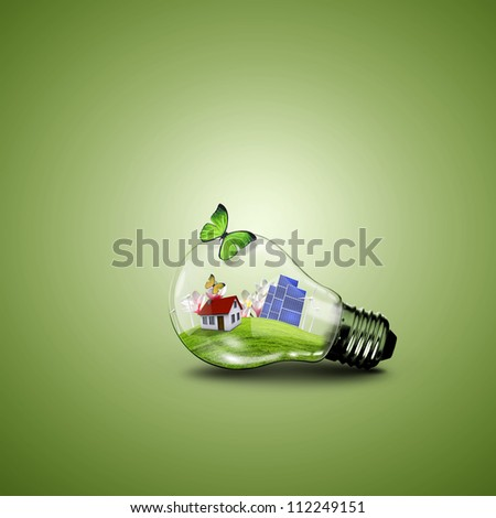 Electric light bulb and house inside it as symbol of green energy - stock photo