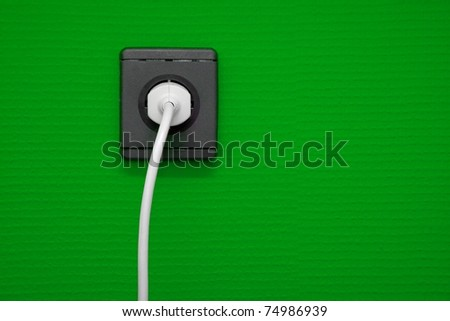 Electric outlet on green wall with cable connected - stock photo