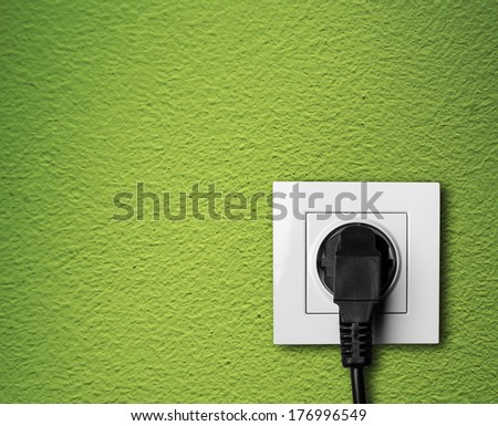 Electric outlet on green wall with cable plugged
