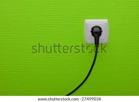 Electric outlet on green wall with cable plugged - stock photo