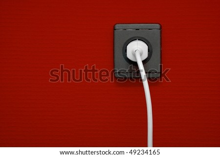 Electric outlet on red wall with cable connected
