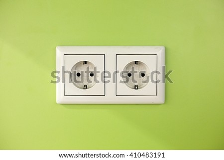 Electric outlets on green wall - stock photo