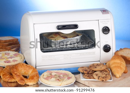 Electric oven-toaster on a reflective surface with diversity of baked and toasted food