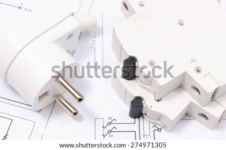 Electric plug and fuse lying on construction drawing of house, accessories for engineering work, energy concept - stock photo