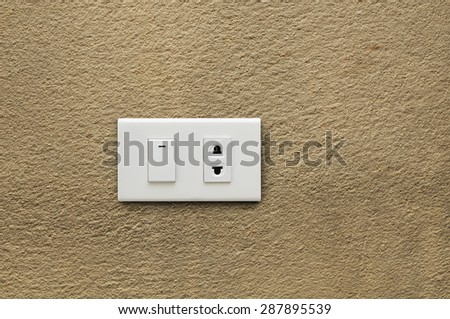 electric plug and switch on wall on brown wall background - stock photo