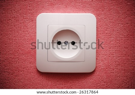 Electric plug connector (outlet) on red wall - stock photo