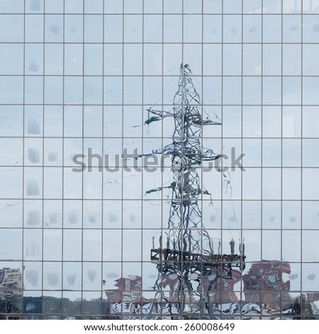 electric pole, houses reflected in windows of office building background - stock photo