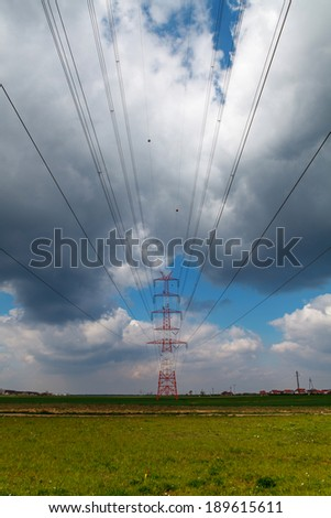 Electric pole under cloudy sky