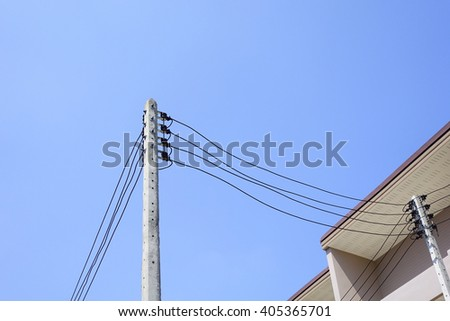 Electric pole with electric line on building and sky background:select focus with shallow depth of field. - stock photo
