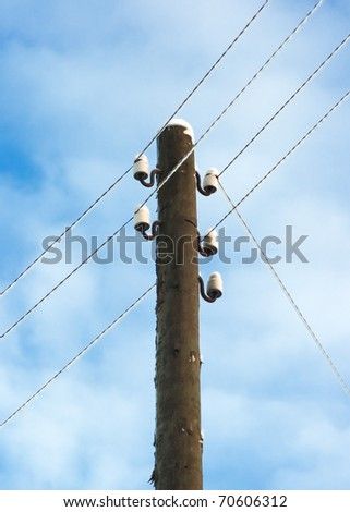 Electric pole with wires on a background of blue sky.