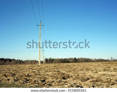 Electric posts across a plowed field, daytime shot with selective focus - stock photo