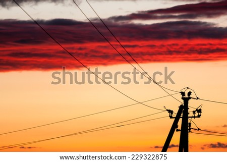 Electric power line against colorful sky at sunset - stock photo