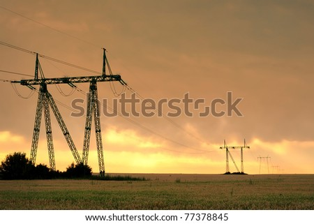 Electric power line in the cultivated field against vivid sunset sky