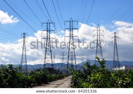 Electric power line towers against cloudy blue sky. - stock photo