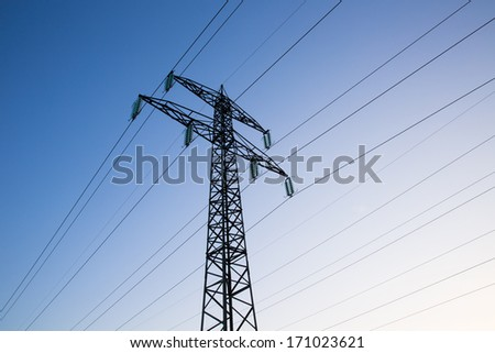Electric power lines and pylon against blue sky - stock photo