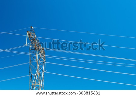 Electric power lines and pylon against blue sky. - stock photo