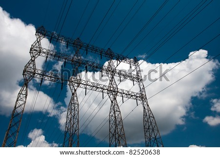 Electric power lines on a blue sky background - stock photo