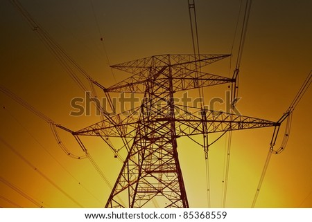 Electric power lines on the golden sky background - stock photo