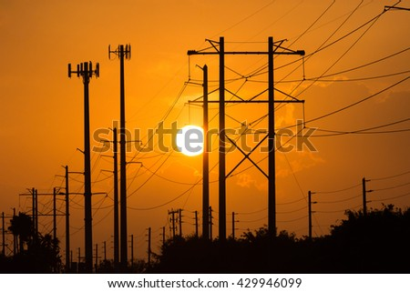 Electric power lines silhouetted against a orange sunset