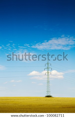 Electric power pole in a beautiful country field