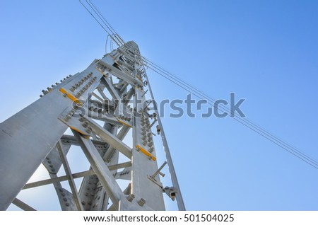 Electric power tower against blue sky