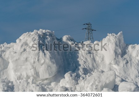 Electric Power Tower Behind Large Pile of Snow with copy space - stock photo