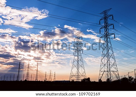 Electric power towers in blue sky before Sun set - stock photo