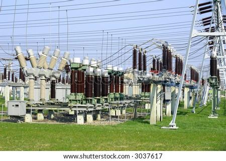Electric power transformation substation with blue sky and green grass - stock photo