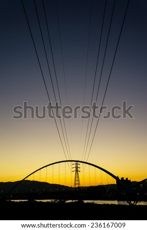 electric power wire through the sky with bridge at sunset time - stock photo