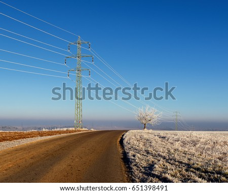 Electric pylon in landscape. Sunny cold winter scene with tree and road on the outskirts of village. High voltage power lines in Czech republic.