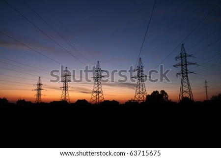 Electric pylons at sunset - stock photo