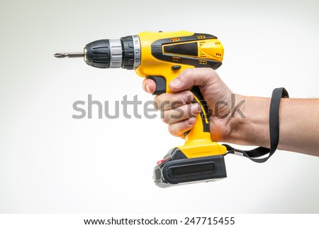 electric screwdriver in his hand - stock photo