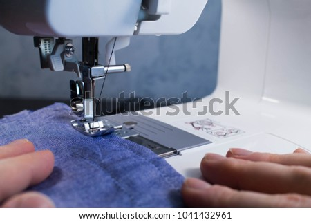 Electric sewing machine, cloth and hands.