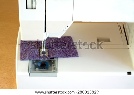 Electric sewing machine on brown wood table indoor closeup