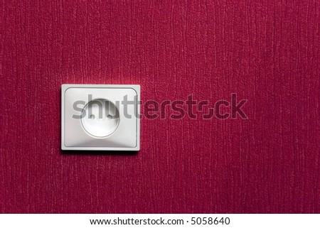 electric socket in the red wall - stock photo